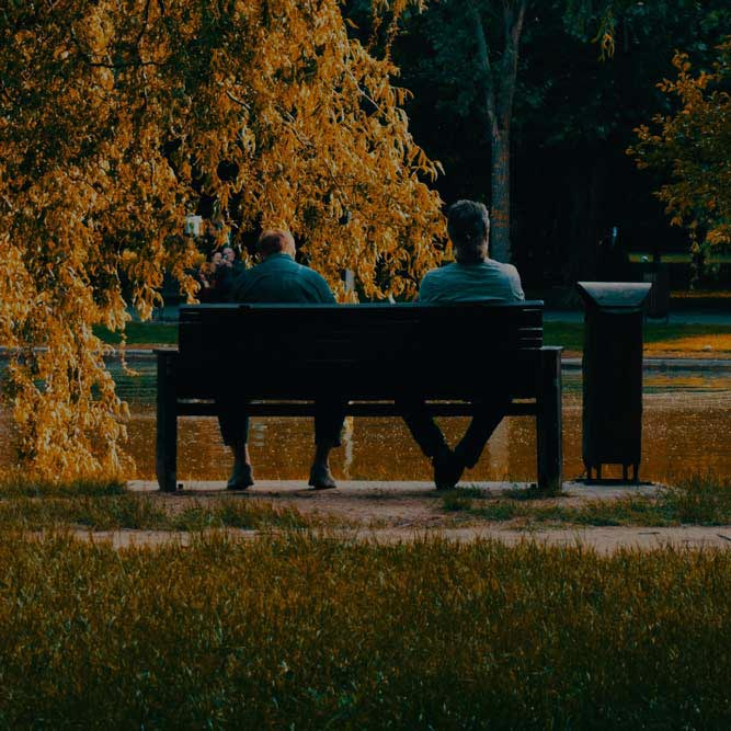 Two people sitting on a bench in a park