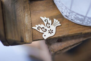 A stylized cutout of a dove on the edge of a table